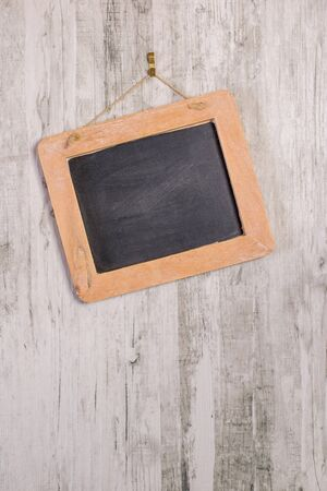 A wooden framed blackboard hanging at an angle on a rustic background with copy space for your text or picture Banco de Imagens