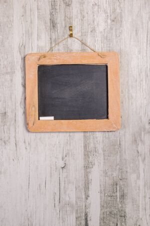 A wooden framed blackboard with chalk hanging on a rustic background with copy space for your text Banco de Imagens