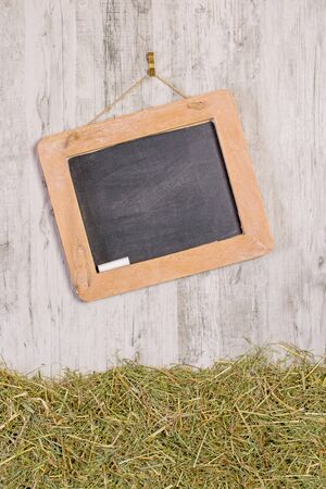 A wooden framed blackboard with chalk hanging at an angle on a rustic background with straw and copy space for your text or picture Banco de Imagens