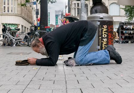 NIEDERSACHSEN, GERMANY SEPTEMBER 26, 2015: A poor man kneeling on the ground with cap in hand begging for money in a large city center pedestrian precinct. Editorial