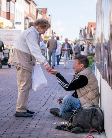 NIEDERSACHSEN, GERMANY JUNE 10, 2015: A lady giving money to a homeless man begging on the street