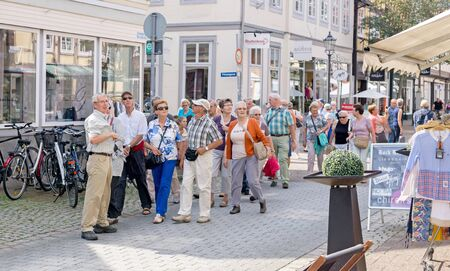 NIEDERSACHSEN, GERMANY AUGUST 26, 2015: A party of tourists being shown around a town by their tour guide. Sajtókép