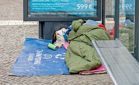 BERLIN, GERMANY JANUARY 1, 2016: A homeless man asleep in a sleeping bag on the ground in a bus shelter Editorial