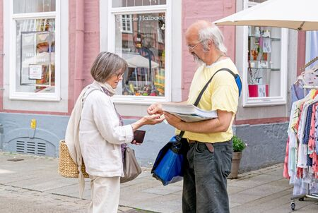 NIEDERSACHSEN, GERMANY JUNE 13, 2015: A female shopper buying a newspaper from a male vendor in the street. Editorial