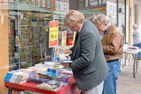 NIEDERSACHSEN, GERMANY JUNE 20, 2015: Male customers looking through books on sale from a table outside a book shop. Editorial
