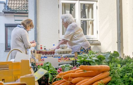 NIEDERSACHSEN, GERMANY AUGUST 21, 2015: An elderly lady selling fresh produce to a female customer at her market stall.