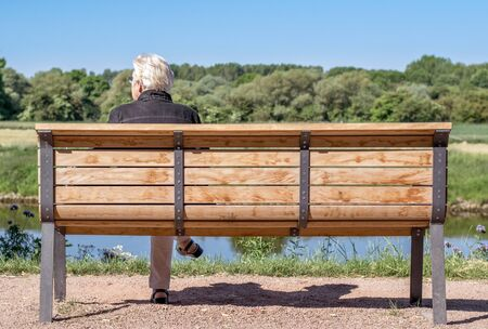 NIEDERSACHSEN, GERMANY JUNE 10, 2015: A single elderly woman sitting on a wooden bench in the countryside looking lonely