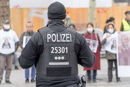 BERLIN, GERMANY APRIL 13, 2019: A German police officer standing in front of a group of protestors in Berlin during a silent demonstration for Abdullah Oecalan