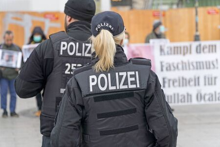 BERLIN, GERMANY APRIL 13, 2019: A German female police officer standing in front of a group of protestors in Berlin during a silent demonstration for Abdullah Oecalan