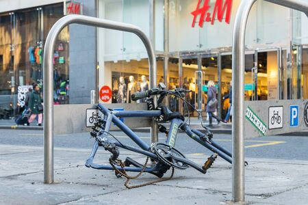GLASGOW, UNITED KINGDOM JANUARY 23, 2019: Bicycle crime concept with a chained up bicycle in a city center that has been stripped of parts Editorial