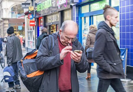 GLASGOW, UNITED KINGDOM JANUARY 23, 2019: A man in the street looking stressed and confused using his mobile phone while smoking a cigarette.