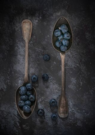 Flat lay image of two vintage silver spoons with blueberries on a dark low light moody background
