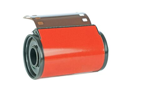 A red roll of 35mm analogue camera film on a white background with copy space for your text Standard-Bild