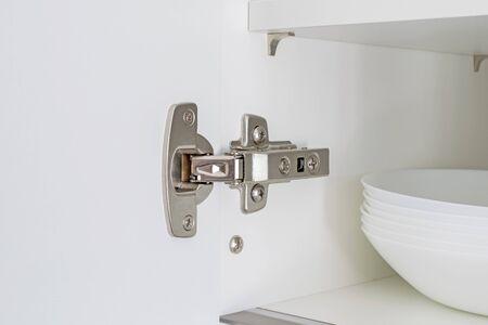 A fitted door hinge inside a white kitchen cupboard Reklamní fotografie