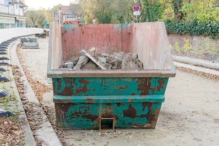 A skip container in roadworks building site with concrete rubble
