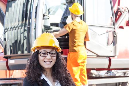 junkyard: young female engineer posing in junkyard with a worker