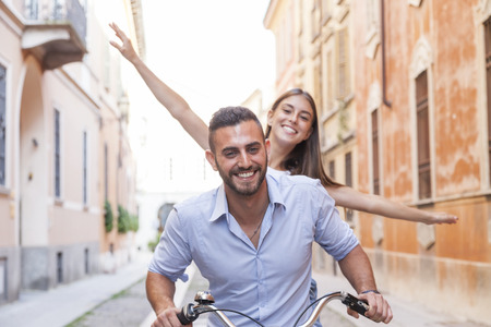 funny bearded man: young loving couple cycling through the city Stock Photo