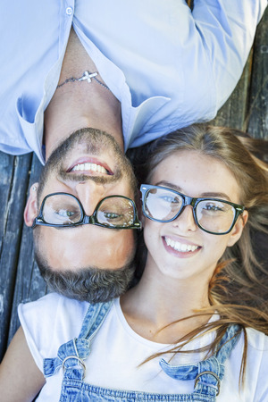girl glasses: portrait of young couple lying on wooden bench Stock Photo
