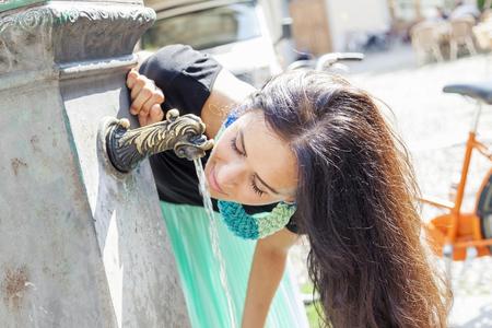 chicas sonriendo: retrato de la muchacha bonita que bebe el agua de la fuente en la ciudad de verano Foto de archivo
