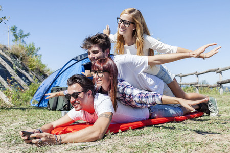 four people: young boys and girls in campsite piled up smiling