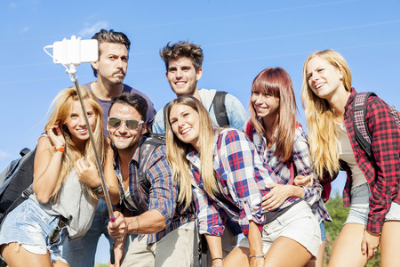 self   portrait: group of friends taking a self portrait with selfie stick