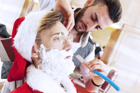 peluquero: Pap� Noel cort� la barba de su peluquero personal