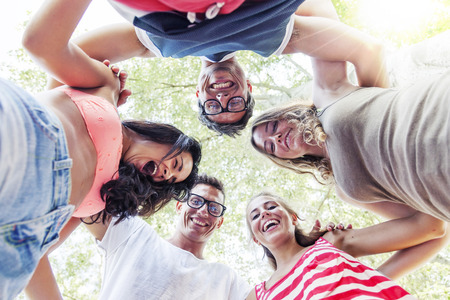 people laughing: group of smiling friends in circle - bottom view Stock Photo