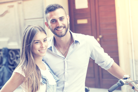 funny bearded man: young couple in love with bike around the city