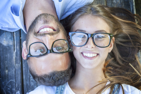 man with glasses: portrait of young couple lying on wooden bench Stock Photo