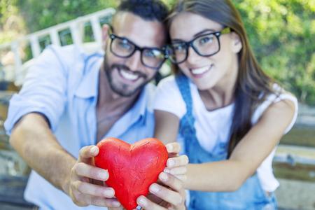 persona feliz: pareja joven que muestra un corazón como símbolo de amor