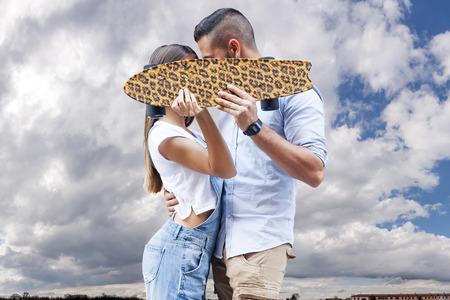 jovenes enamorados: joven pareja besándose esconderse detrás de una tabla de skate Foto de archivo