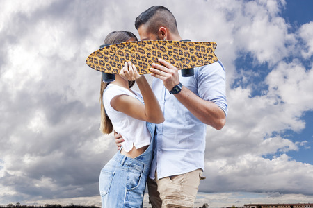 young caucasian: young couple kissing hiding behind a skateboard
