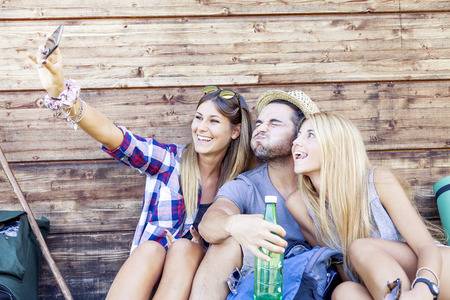 group picture: group of smiling friends taking funny selfie with smart phone