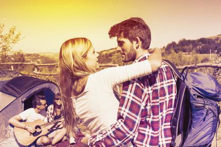 mochila viaje: joven pareja bes�ndose en un camping de la colina en una mirada del color del vintage filtrada Foto de archivo