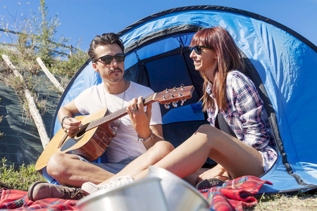 ragazza innamorata: couple of young lovers enjoy playing guitar at the campsite