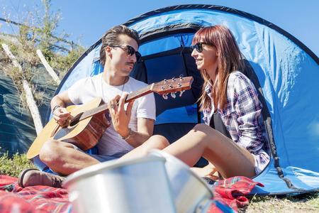 ni�o con mochila: par de j�venes amantes disfrutan tocando la guitarra en el camping Foto de archivo