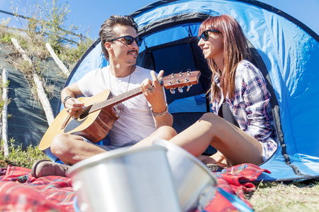 campsite: couple of young lovers enjoy playing guitar at the campsite