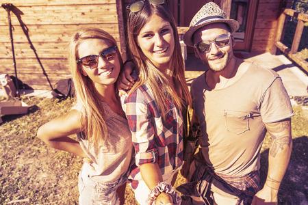 chicas sonriendo: grupo de amigos sonrientes que toman selfie divertido con el tel�fono inteligente en un color filtrada aspecto c�lido de la vendimia