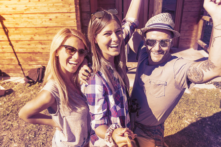 party friends: group of smiling friends taking funny selfie with smart phone on a vintage warm color filtered look