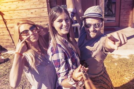 暖かいビンテージ色フィルターの外観上スマート フォンと selfie を取って笑顔の友人のグループ 写真素材