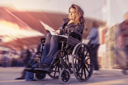 silla de rueda: se�ora joven en una silla de ruedas en busca de un destino en el mapa