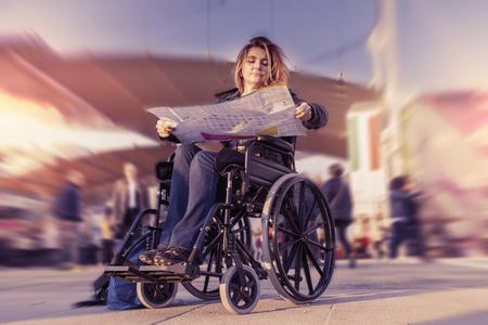 paraplegico: señora joven en una silla de ruedas en busca de un destino en el mapa