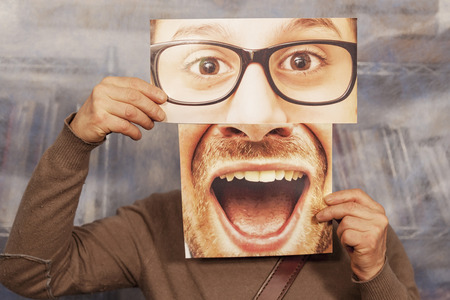 man holding a card with a big smile and big glasses on it Stock Photo