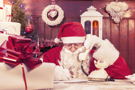 old man: portrait of santa claus on the phone at his home compiles the wishlist for christmas Stock Photo