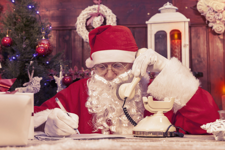 wishlist: portrait of santa claus on the phone at his home compiles the wishlist for christmas Stock Photo