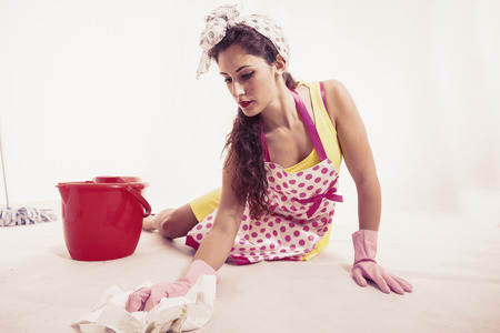 floor cloth: pretty housemaid with cloth and bucket cleaning the floor warm look
