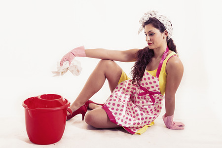 charlady: pretty housemaid with cloth and bucket cleaning the floor