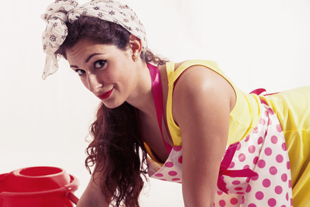 housemaid: pretty housemaid with cloth and bucket cleaning the floor