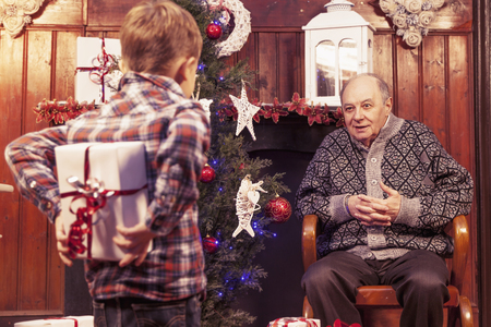 gift behind back: little boy hiding christmas gift for his grandfather behind back Stock Photo