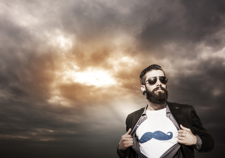 dressing up costume: young hipster superhero monitors under a dark sky